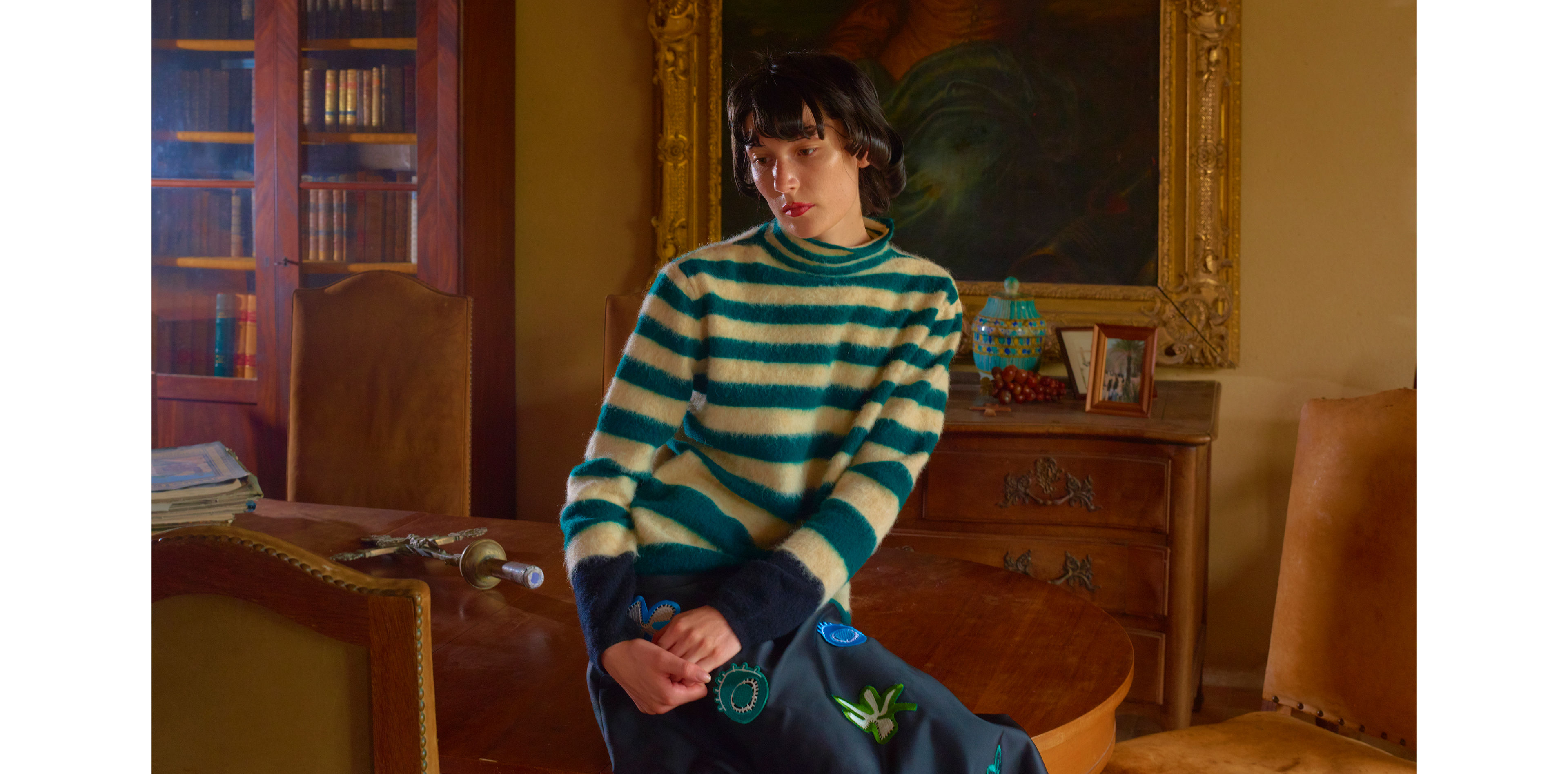 Model wears a green and white striped sweater in an alpaca-wool blend with a black skirt with appliqué details