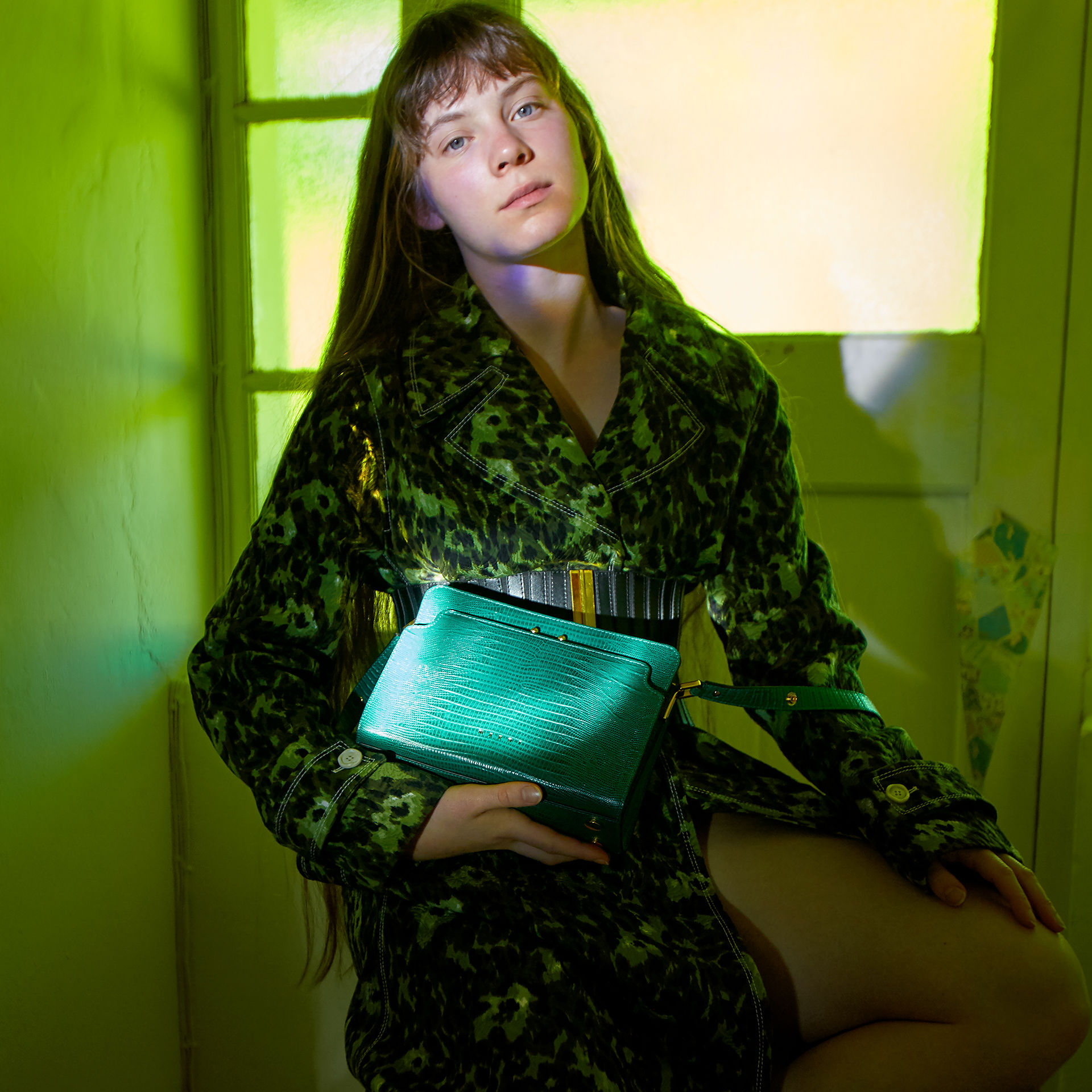 Model is wearing the lizard-printed jade green Trunk Reverse bag