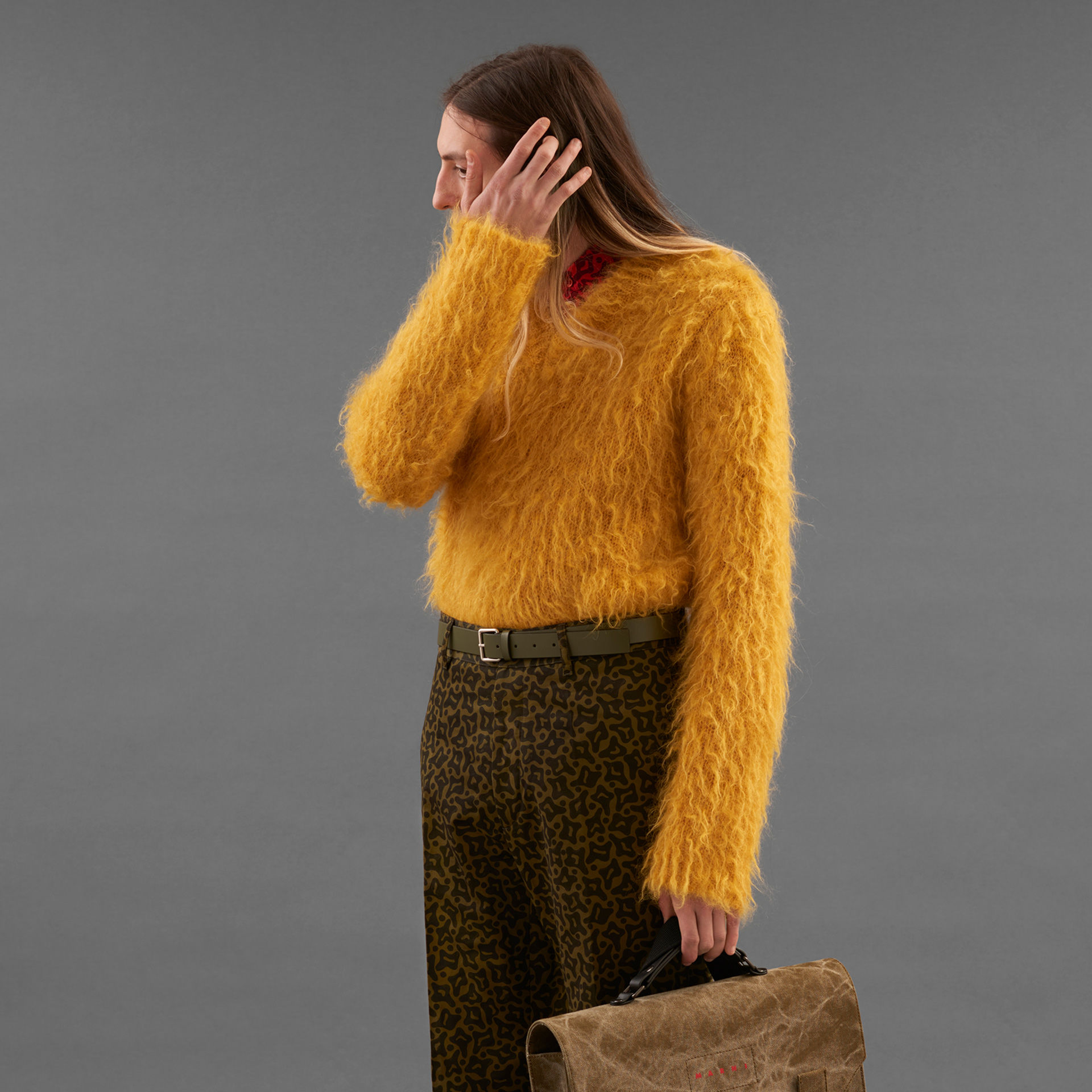 Model wears yellow brushed sweater and camo print pants