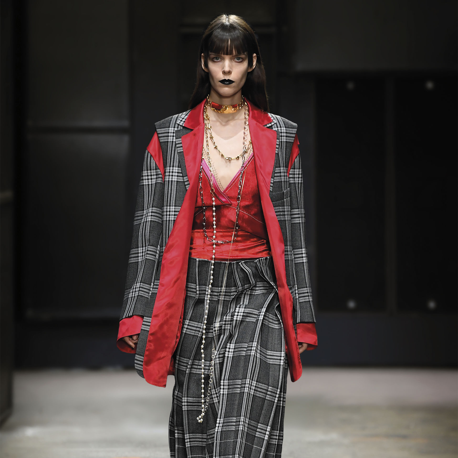 Model wears a red plaid jacket and skirt