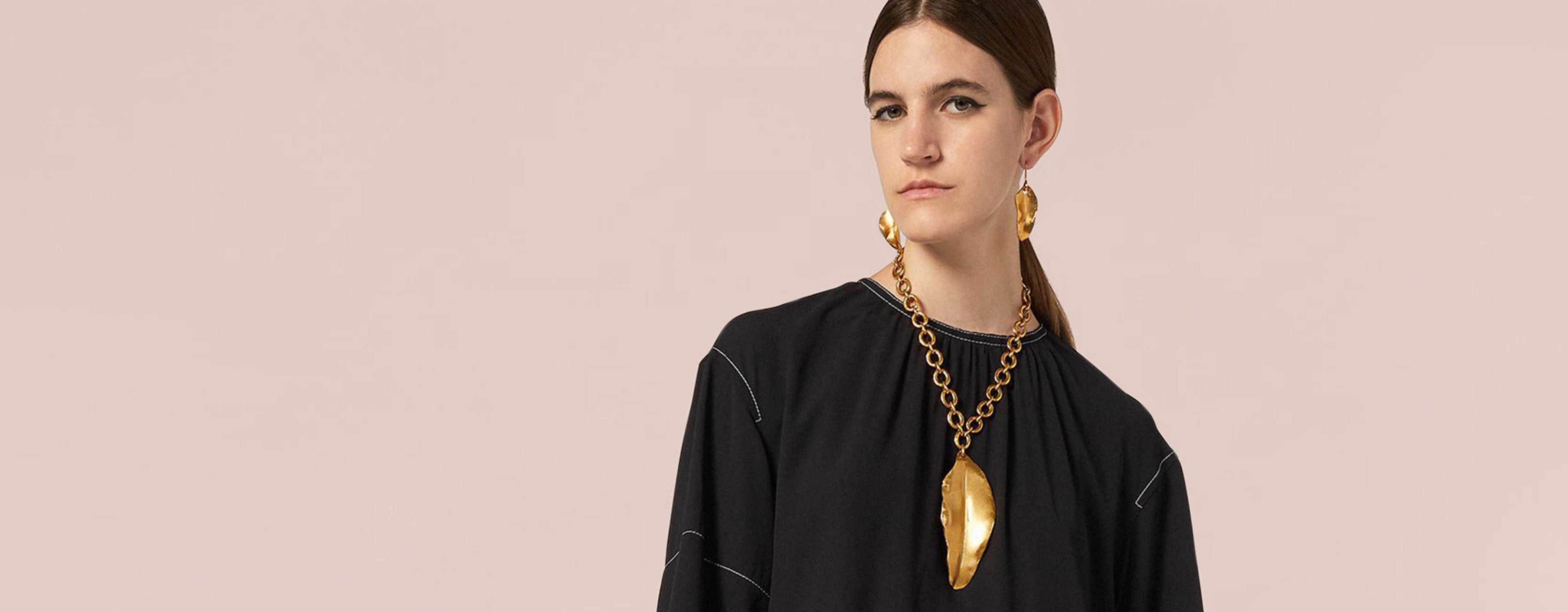 Model wears a floral-printed dress and a chain necklace with a golden leaf