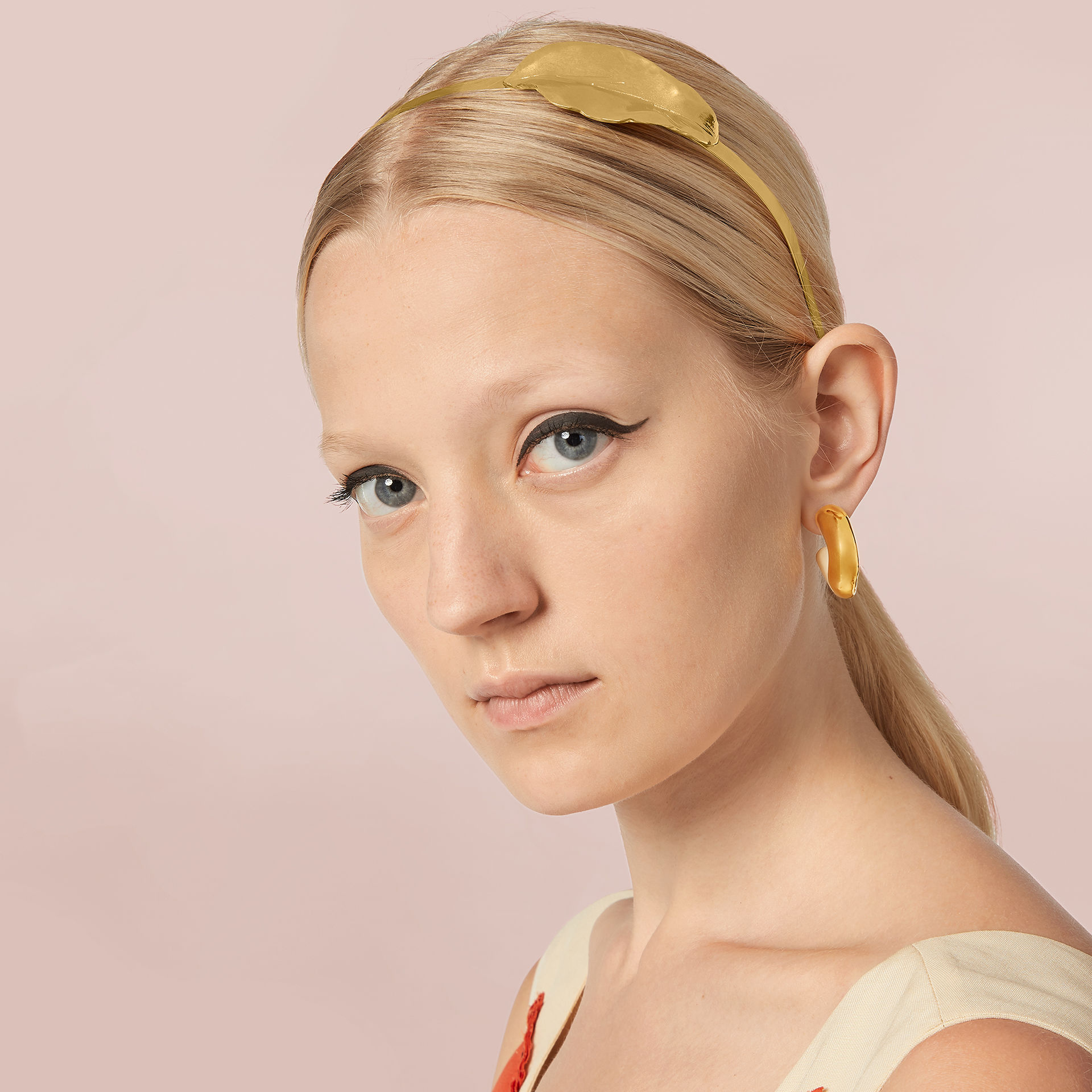 Model wears a golden headband with a leaf decoration