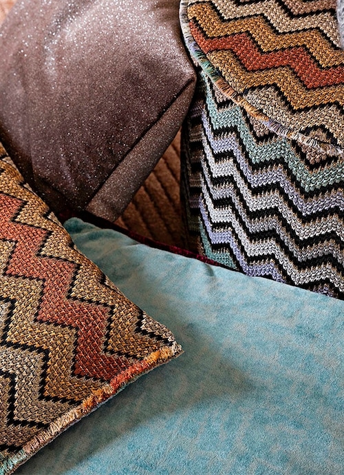 Two cushions with metallic shimmer from MissoniHome being placed on the sofa, they have rather similar designs but different in the layout of colors.