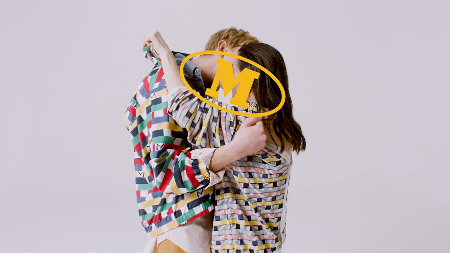 A boy and a girl kissing and holding onto each other, they are both wearing the latest M Missoni collection. There is a giant M logo embedded in front of their faces.