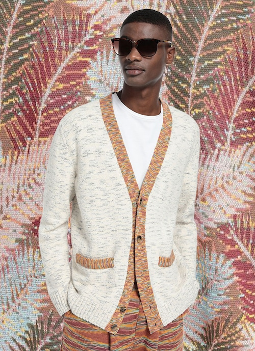 A male model poses in front of a tropical themed backdrop, he is wearing a light color cardigan over a t-shirt and sunglasses/