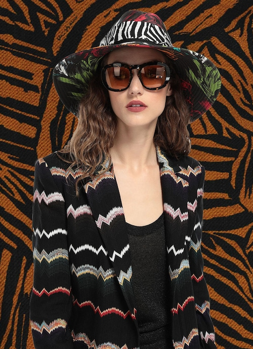 A female model poses in front of a tiger stripe backdrop, she is wearing a dark color blazer over a cami, paired with jungle print fisherman\'s hat and sunglasses.