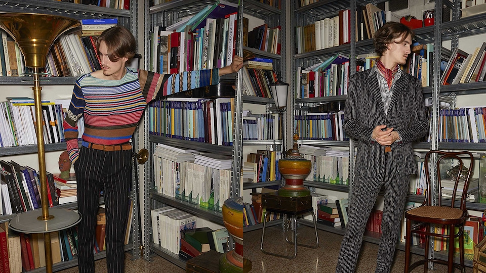 2 models posing in a library in front of the shelves. One is dressed in a casual style with colorful sweather and stripe pants while the other in a full stripe-styled suit.