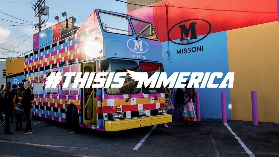 A double decker bus parked in front of a wall at a parking lot in downtown LA, on the wall there is a huge logo of M Missoni and the bus is also painted in M Missoni\'s iconic colors for this season.